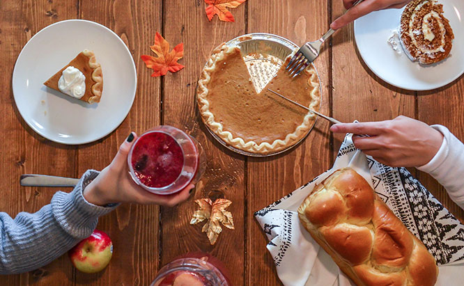 Image of people slicing pie and passing wine on a Thanksgiving table with various dishes.